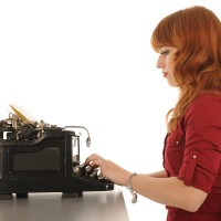 Woman at the office with very old black typewriter