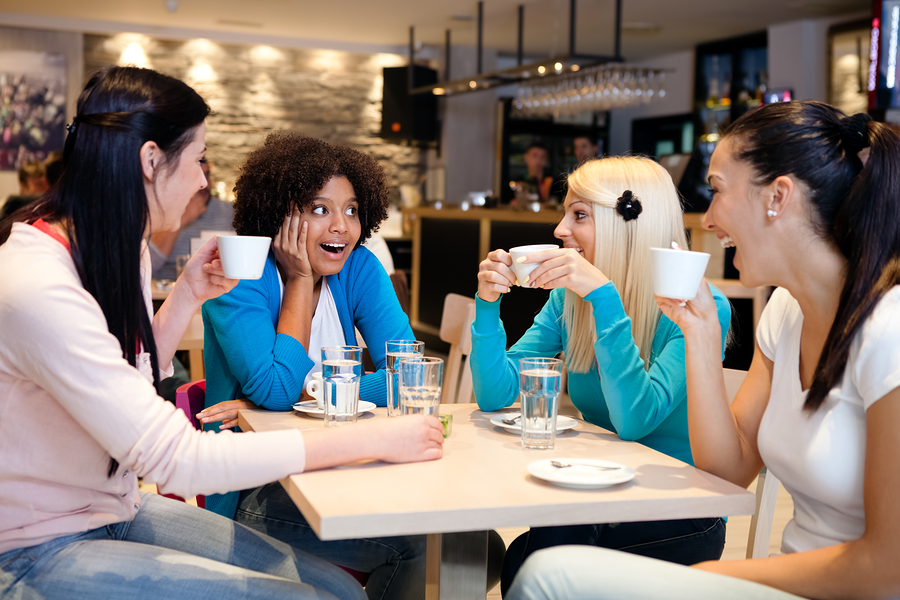 Four female friends enjoying in talking at cafe